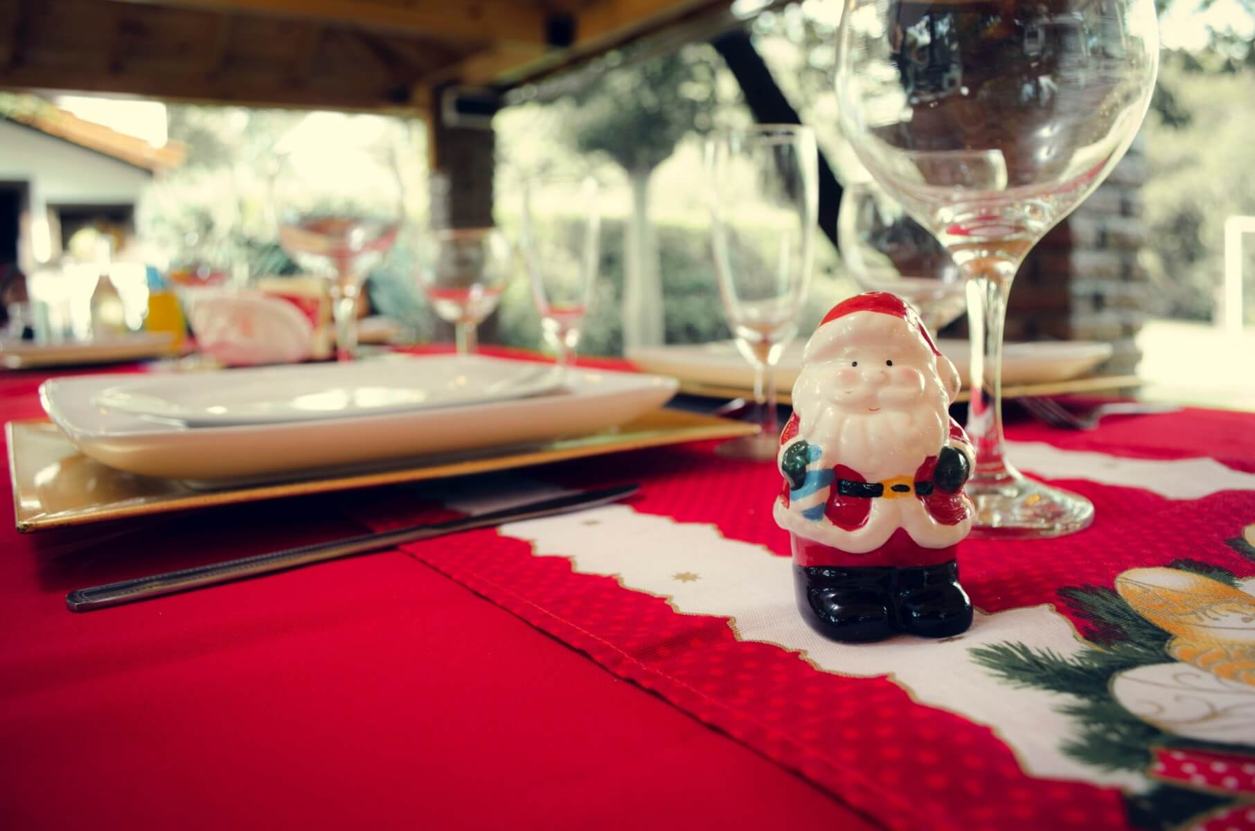 santa-claus-ceramic-figurine-next-to-wine-glasses-and-white-824306